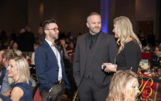 Two men in suits talking with blonde woman