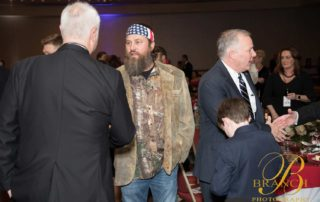 Willie Robertson shaking hands with man in black suit