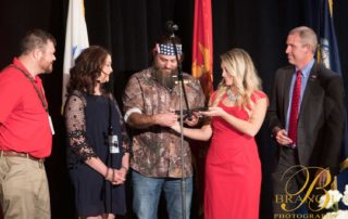 Woman showing Willie Robertson an object on stage
