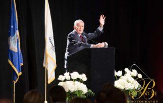 Older gentleman raising hand during speech at gala