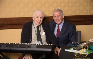 Two older gentlemen sitting behind keyboard