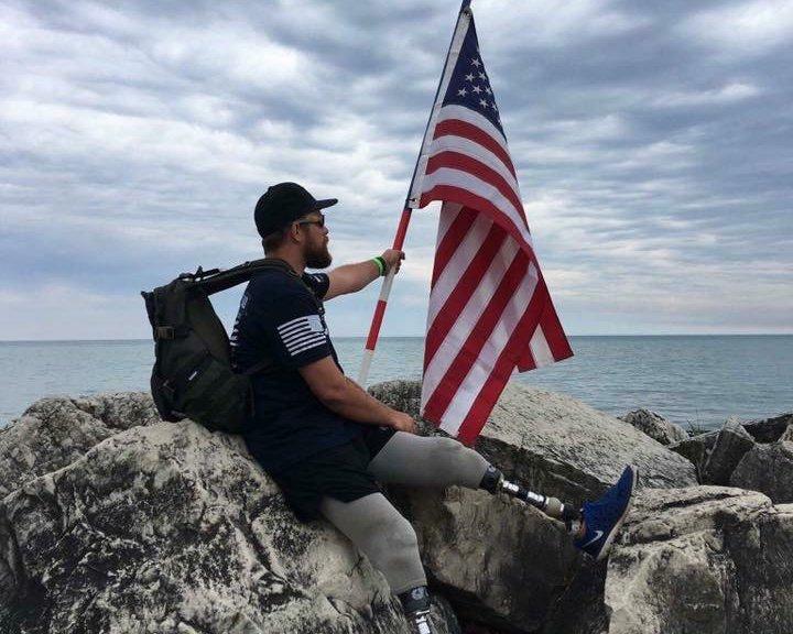 Scott West holding an American flag near ocean.