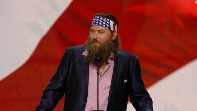 Willie Robertson talking in front of an American flag